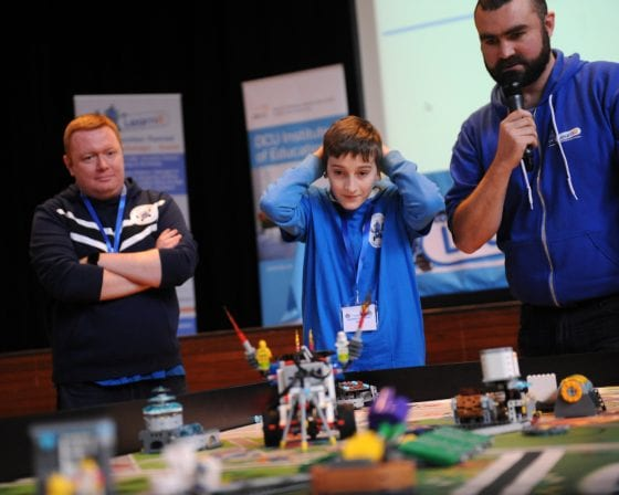 Ross Maguire from Learnit, Diarmuid McNamara a teacher from Rosmini Community School and a student watch a robot compete.